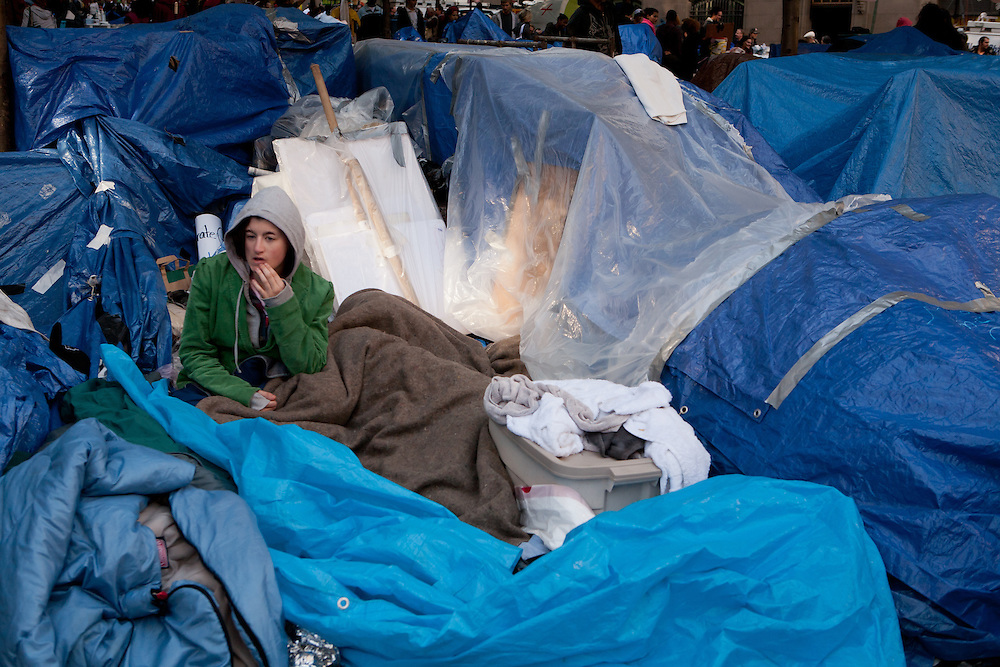 A tired protester rests among piles of belongings covered in blue plastic tarps.