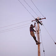 A man fixes electrical wires in Kesavapalayam, a Dalit fishing village in Tamil Nadu, India, on January 16, 2005, after the area was struck by the Indian Ocean Tsunami on December 26, 2004. Generated by an earthquake on the ocean floor, the tsunami devastated the fishing industry along the southeastern coast of India.