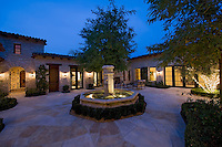 House exterior at night with a fountain  patio furniture and trees  one in which is lit with fairy lights