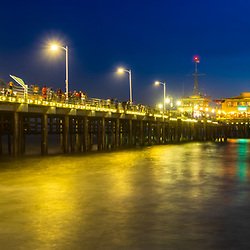 Santa Monica Pier at night panoramic photo in blue and gold. Copyright ⓒ 2017 Paul Velgos with All Rights Reserved.