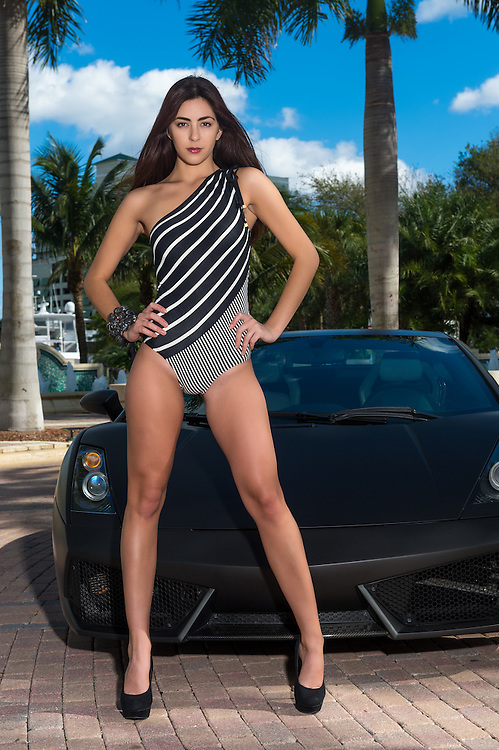 Young and sensual caucasian woman wearing swimsuit posing in front of a sport car