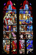 Stained glass window with at the top, a prince and princess offered bread and salt on arrival at Marchais castle and below, Prince Rainier and Prince Albert of Monaco with their coat of arms, 1975, in the Grimaldi Chapel in the Basilica of Liesse Notre Dame, built 1134 in Flamboyant Gothic style by the Chevaliers d'Eppes, then rebuilt in 1384 and enlarged in 1480 and again in the 19th century, Liesse-Notre-Dame, Laon, Picardy, France. Pilgrims flock here to worship the Black Virgin, based on Ismeria, the Soudanese daughter of the sultan of Cairo El-Afdhal, who saved the lives of French knights during the Crusades, converted to christianity and married Robert d'Eppes, son of Guillaume II of France. Picture by Manuel Cohen