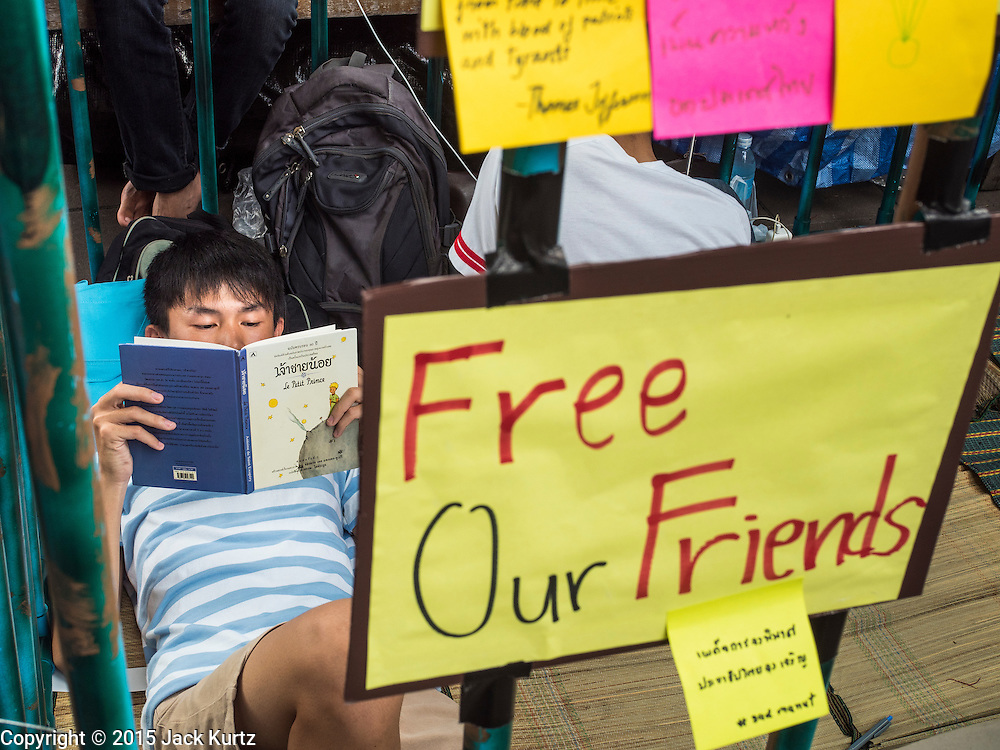 "06 JULY 2015 - BANGKOK, THAILAND: A student reads a book in a mock jail cell to call attention to the plight of other students arrested for charges related to political assembly. More than 100 people gathered at Thammasat University in Bangkok Monday to show support for 14 students arrested two weeks ago. The students were arrested for violating orders against political assembly. They face criminal trial in military courts. The students' supporters are putting up ""Post It"" notes around Bangkok and college campuses up country calling for the students' release.      PHOTO BY JACK KURTZ"