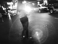 Street prostitute swallowed in the headlights of a passing car on Mabini Street, Ermita, Manila, Philippines.   The area of Ermita is experiencing a resurrgence of street prostitution after a Christian mayor had closed down most of the girly bars in the 1990's, Manila, Philippines.