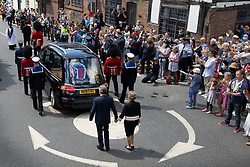 © Licensed to London News Pictures. 10/07/2020. Ditchling, UK. People applaud as the funeral cortege carrying the body of WWII Forces' Sweetheart Dame Vera Lynn passes through her home village of Ditchling, East Sussex followed on foot by her daughter Virginia Lewis-Jones and husband Tom. The cortege will head to a crematorium in Brighton for a private funeral. A Battle of Britain Memorial Flight flypast, consisting of a Spitfire and a Hurricane, will perform a flypast at noon. Photo credit: Peter Macdiarmid/LNP