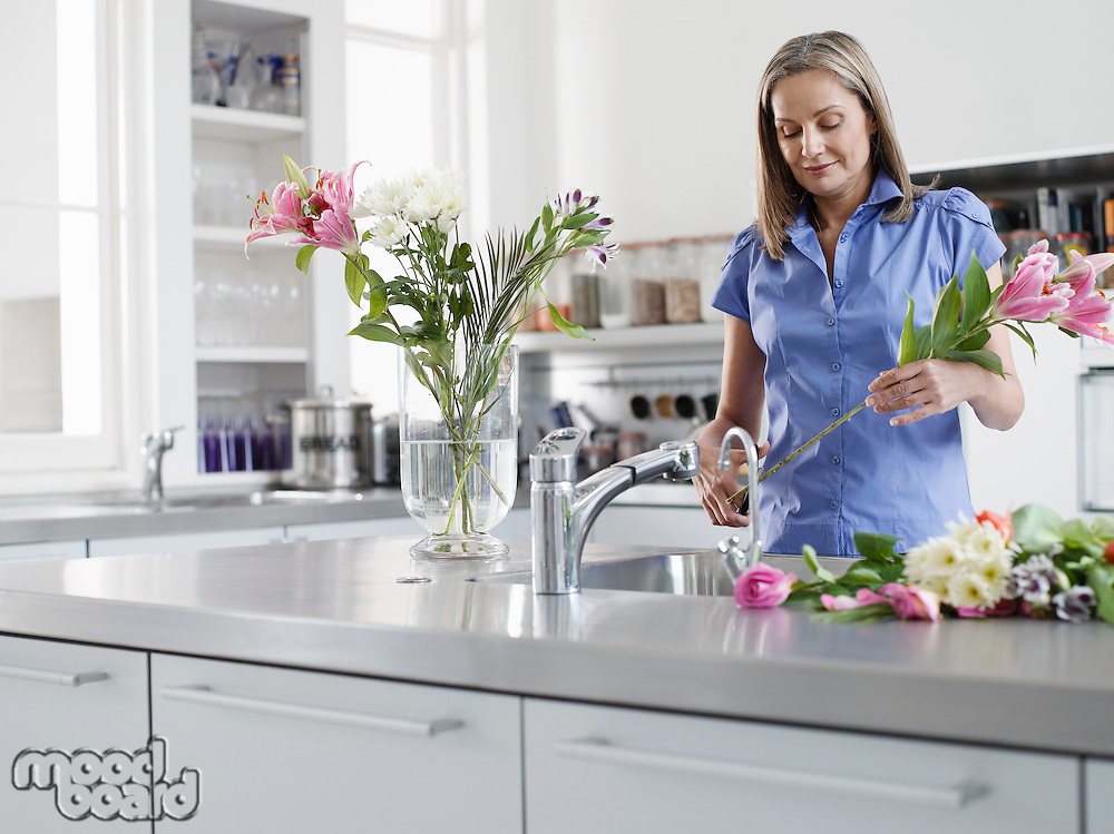 Mid-adult woman at kitchen sink preparing flowers to be put in vase