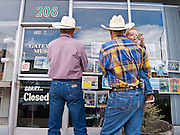 29 JULY 2005 - WILLIAMS, ARIZONA, USA: Ranchers windowshop in downtown Williams, AZ, July 29. Williams, a small ranching town in northern Arizona and about an hour from the south entrance to the Grand Canyon National Park, has reinvented itself as a tourist destination. The town draws tourists going to the park and tourists who want to experience American western lifestyle. The town hosts the largest amateur rodeo in Arizona drawing contestants and spectators from across the state. PHOTO BY JACK KURTZ