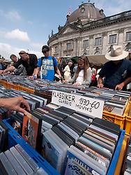People browsing second hand movies at outdoor weekend flea market beside Museumsinsel or Museums Island in Mitte Berlin Germany