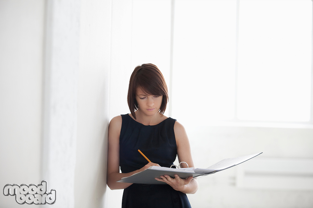 Business woman on writes in file in empty warehouse
