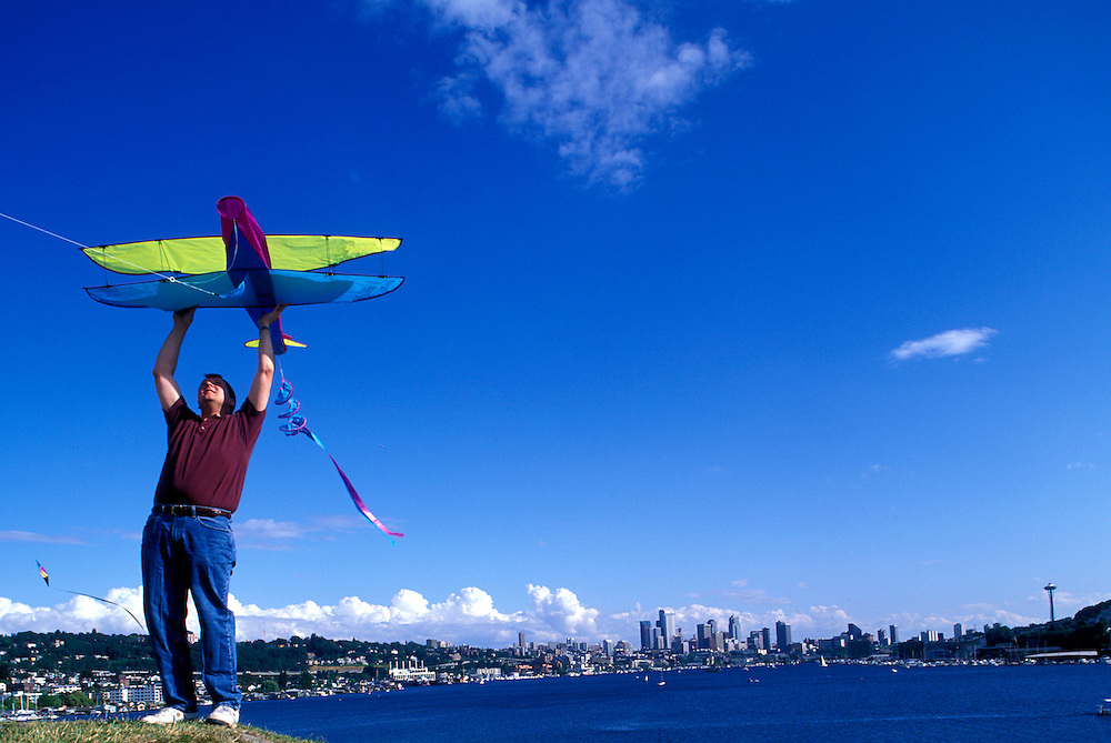 USA, Washington, Seattle, Man launches kite from top of hill at Gas Works Park on summer afternoon along Lake Union