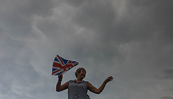 © Licensed to London News Pictures.22/08/15<br /> Castle Howard, North Yorkshire, UK. <br /> <br /> A woman dances under gathering storm clouds as hundreds of people attend the 25th anniversary of the Castle Howard Proms event near York. The theme of the event this year is a commemoration of the 75th anniversary of the Battle of Britain and the 70th anniversary of VE day and brings an evening of classic musical favourites celebrating Britishness to the lawns of Castle Howard.<br /> <br /> Photo credit : Ian Forsyth/LNP