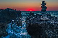 Tower of rounded stones by the sea at sunset