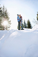 Couple standing on snow-covered hill low angle view