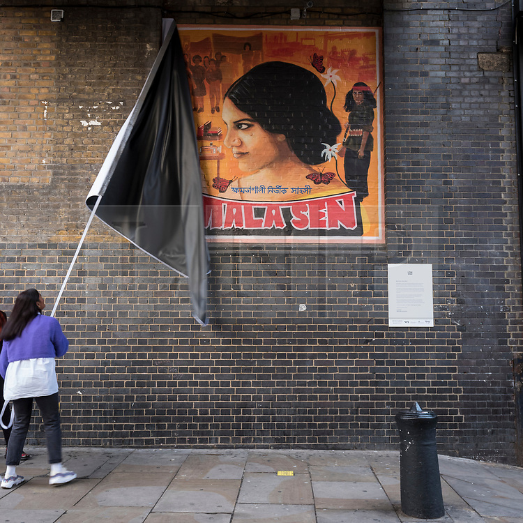 © Licensed to London News Pictures. 18/10/2018. LONDON, UK. Artist Justine Sehra unveils a new artwork in Brick Lane. The artwork features human rights activist Mala Sen and is one of 20 newly-commissioned artworks, designed by the London Tate Collective team, Tate's group for 16 to 25 year old artists, which will appear in public spaces across the city marking the centenary of women's suffrage.  Called LDN WMN, the artworks celebrate women who have played a crucial role in London's history, but have been largely overlooked.  Photo credit: Stephen Chung/LNP