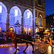 A horse-drawn carriage with tourists passes by the front of the Notre Dame Basilica and angel lights decorate the main entrace of the Basilique Notre-Dame de Montreal for Christmas.