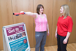 Fitness instructor performing a body MOT on a member at her sports leisure centre,