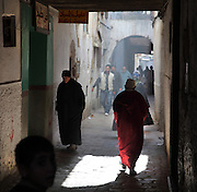 People walking along a narrow street in the medina or old town of Tetouan, on the slopes of Jbel Dersa in the Rif Mountains of Northern Morocco. Tetouan was of particular importance in the Islamic period from the 8th century, when it served as the main point of contact between Morocco and Andalusia. After the Reconquest, the town was rebuilt by Andalusian refugees who had been expelled by the Spanish. The medina of Tetouan dates to the 16th century and was declared a UNESCO World Heritage Site in 1997. Picture by Manuel Cohen