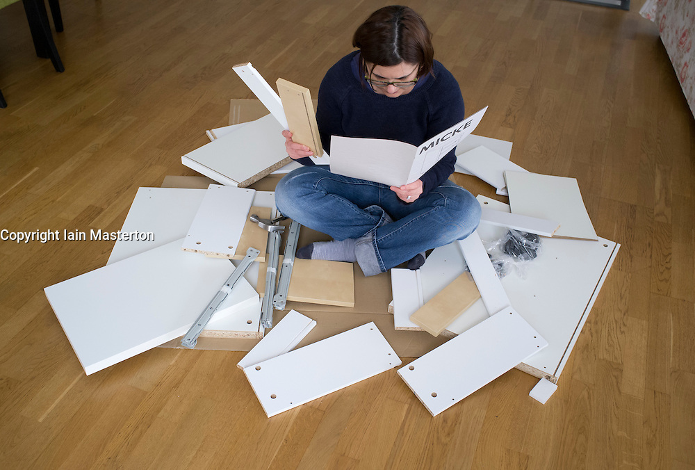 Woman assembling flat-pack furniture from IKEA at home