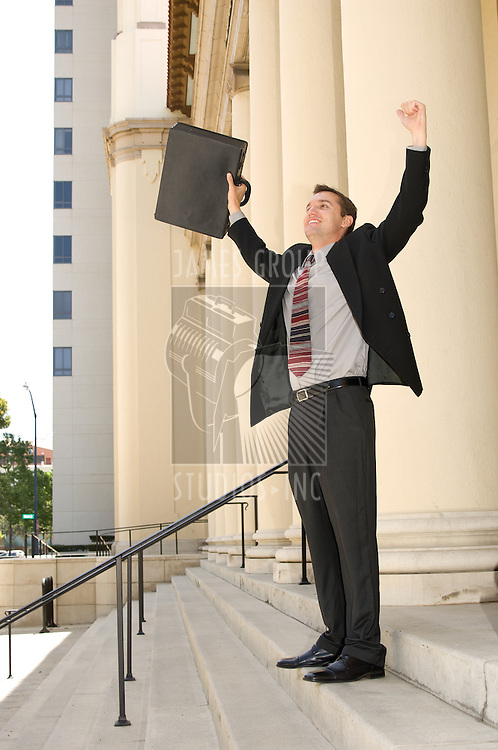 Attorney standing on the courthouse steps with both arms raised in a gesture of victory