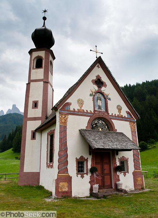 The Baroque, onion-domed Church of St. Johann in Ranui was built in 1744 and dedicated to Saint Johannes Nepomuk. The Geisler/Odle Group mountains rise nearly 1000 meters above the church in Val di Funes (Villnöß valley) in the Dolomites, Italy, Europe.  John of Nepomuk, or Nepomucenea, is a national saint of the Czech Republic. The Dolomites were declared a natural World Heritage Site (2009) by UNESCO.