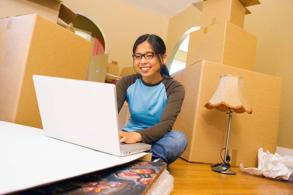 A smiling late 20's Japanese American woman sitting on the floor of her new home using a laptop computer while surrounded by moving boxes and home furnishings.