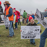 Ivan Weikle makes a face at his father while holding a sign in support of PEIA drawn by Lewisburg Elementary School art teacher Jody Wilber (in hat) along Route 219 in Lewisburg, W.V., on Monday, February 26, 2018 on the third day of the statewide walkout by school personnel.