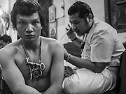 """07 MARCH 2015 - NAKHON CHAI SI, NAKHON PATHOM, THAILAND: A man gets a spiritual tattoo at the Wat Bang Phra tattoo festival. Wat Bang Phra is the best known """"Sak Yant"""" tattoo temple in Thailand. It's located in Nakhon Pathom province, about 40 miles from Bangkok. The tattoos are given with hollow stainless steel needles and are thought to possess magical powers of protection. The tattoos, which are given by Buddhist monks, are popular with soldiers, policeman and gangsters, people who generally live in harm's way. The tattoo must be activated to remain powerful and the annual Wai Khru Ceremony (tattoo festival) at the temple draws thousands of devotees who come to the temple to activate or renew the tattoos. People go into trance like states and then assume the personality of their tattoo, so people with tiger tattoos assume the personality of a tiger, people with monkey tattoos take on the personality of a monkey and so on. In recent years the tattoo festival has become popular with tourists who make the trip to Nakorn Pathom province to see a side of """"exotic"""" Thailand.   PHOTO BY JACK KURTZ"""