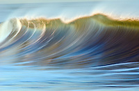 A large wave breaking at sunrise with motion in Ventura Harbor, California.