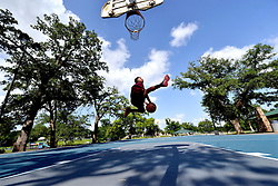 Derion Morriel soars through the air while attempting a shot during an afternoon of basketball practice at Sue Haswell Park on Tuesday.  Morriel said he was excited to see clear skies so he could get out and play and enjoy the sun.