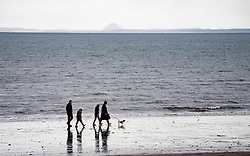 Portobello, Scotland, UK. 28 March, 2020. On the first weekend of the coronavirus lockdown the public were outdoors exercising and maintaining social distancing along Portobello beachfront promenade. Pictured; Family walking on Portobello beach, Berwick Law in distance.  Iain Masterton/Alamy Live News