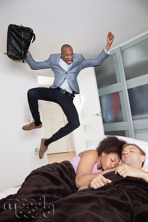 Shocked businessman looking at couple sleeping in bed