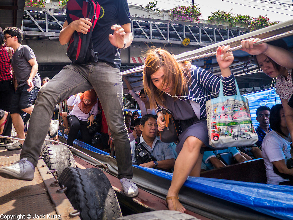 10 OCTOBER 2012 - BANGKOK, THAILAND:  Passengers scramble to get off a canal boat at the AsokPetchaburi Pier. Bangkok used to be criss crossed by canals (called Khlongs in Thai) but most have been filled in and paved over. Khlong Saen Saeb is one of the few remaining khlongs in Bangkok with regular passenger boat service. Boats and ships play an important in daily life in Bangkok. Thousands of people commute to work daily on the Chao Phraya Express Boats and fast boats that ply Khlong Saen Saeb. Boats are used to haul commodities through the city to deep water ports for export.     PHOTO BY JACK KURTZ