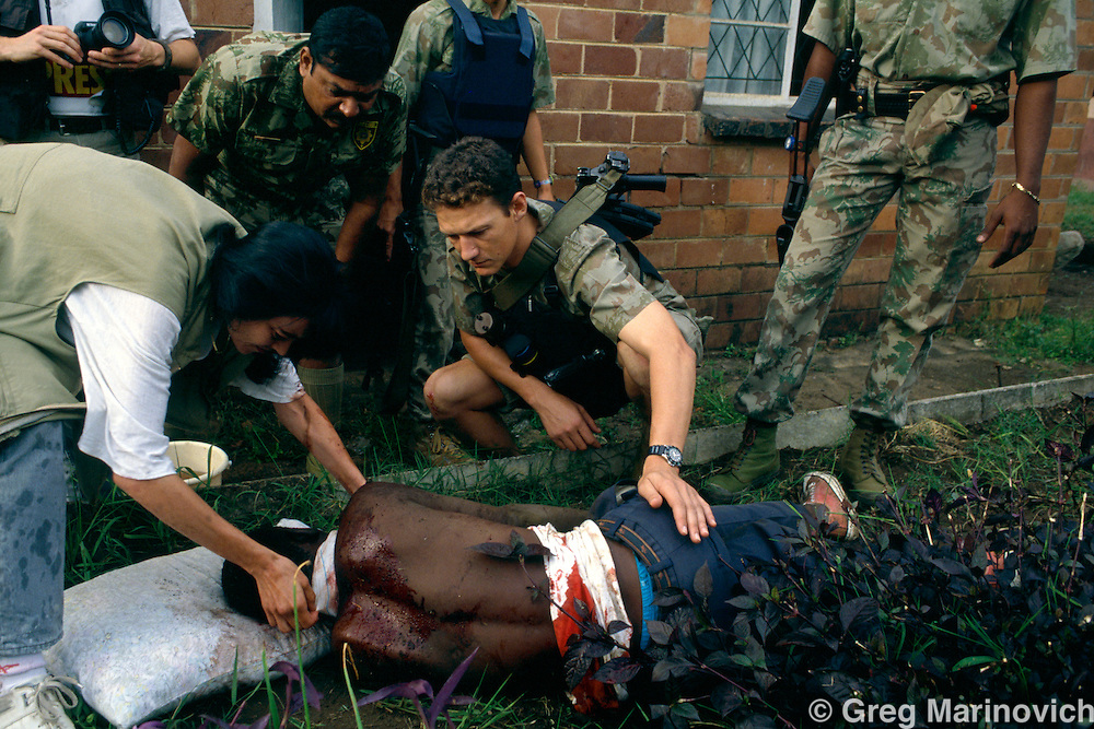 KwaZulu Natal. South Africa. 1994. Riot police treat a man wounded in IFP ANC clashes, KwaMashu,  KwaZulu Natal 1994.
