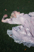 a woman in a period dress is lying in the grass
