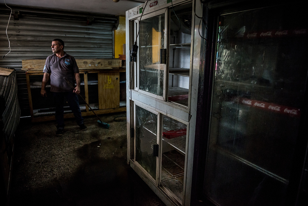 CARACAS, VENEZUELA - APRIL 21, 2017:  Workers clean debris from inside Tintalim supermarket, that was one of over a dozen stores looted late last night in El Valle, a working class neighborhood in Caracas. The streets of Caracas erupted into a night of riots, looting and clashes with National Guardsmen as anger from two days of pro-democracy protests spilled into unrest in working class neighborhoods and slums. Shots rang out throughout the night in El Valle, a neighborhood of mixed loyalties, as armored vehicles struggled to contain crowds of looters. At one point during the night, clashes became so heavy that a nearby children's hospital was evacuated after the ward filled with tear gas. The government said they were responding to an attack on the hospital by opposition protestors.  PHOTO: Meridith Kohut
