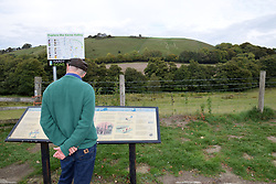 Tourist looking at Cerne Abbas Giant information sign, Dorset, UK. Posed by model