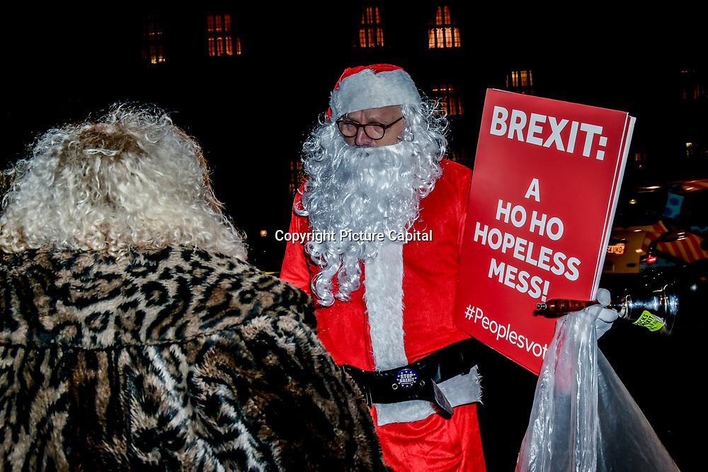 "A Protestors wearing a Santa dress to show solidarity! ""Vote down May's deal"" at Parliament Yard , on 11 December 2018, London, UK."