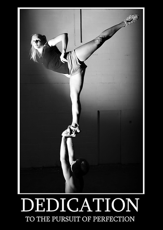 Motivational poster of a single based partner stunt lib with the flyer doing a arabesque stretch in black and white. Caption underneath reads &quot;Dedication to the pursuit of perfection&quot;<br />
