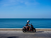 09 DECEMBER 2017 - PATTAYA, CHONBURI, THAILAND: A woman rides her motorcycle on the road in front of Jomtien Beach in Pattaya.  PHOTO BY JACK KURTZ