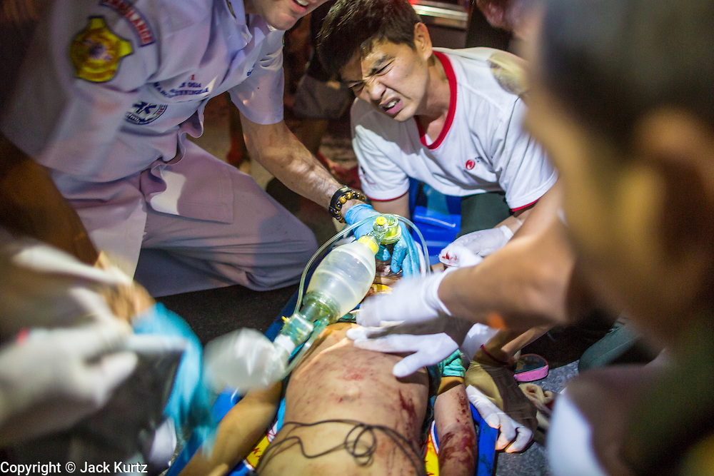 "10 NOVEMBER 2012 - BANGKOK, THAILAND: A Ruamkatanyu Foundation medical team tries to save the life of a boy hit by a vehicle near the Klong Toey slum in Bangkok. The child had severe head injuries and died at the scene. The Ruamkatanyu Foundation was started more than 60 years ago as a charitable organisation that collected the dead and transported them to the nearest facility. Crews sometimes found that the person they had been called to collect wasn't dead, and they were called upon to provide emergency medical care. That's how the foundation medical and rescue service was started. The foundation has 7,000 volunteers nationwide and along with the larger Poh Teck Tung Foundation, is one of the two largest rescue services in the country. The volunteer crews were once dubbed Bangkok's ""Body Snatchers"" but they do much more than that now.    PHOTO BY JACK KURTZ"