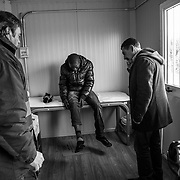 Mr Frangella, doctor voluunteer (on the right) visiting a patient in a small container of Caritas; on the left Emilio of Caritas assisting him