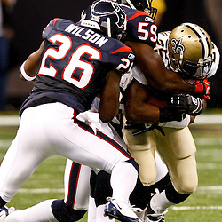 August 21, 2010; New Orleans, LA, USA; New Orleans Saints running back Reggie Bush (25) is tackled by Houston Texans linebacker DeMeco Ryans (59) and safety Eugene Wilson (26) during the first quarter of a preseason game at the Louisiana Superdome. Mandatory Credit: Derick E. Hingle