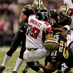 2009 November 02:  New Orleans Saints defenders Jabari Greer (32) and Roman Harper (41) and Jonathan Vilma (51) combine to tackle Atlanta Falcons tight end Tony Gonzalez (88) during a game at the Louisiana Superdome in New Orleans, Louisiana.