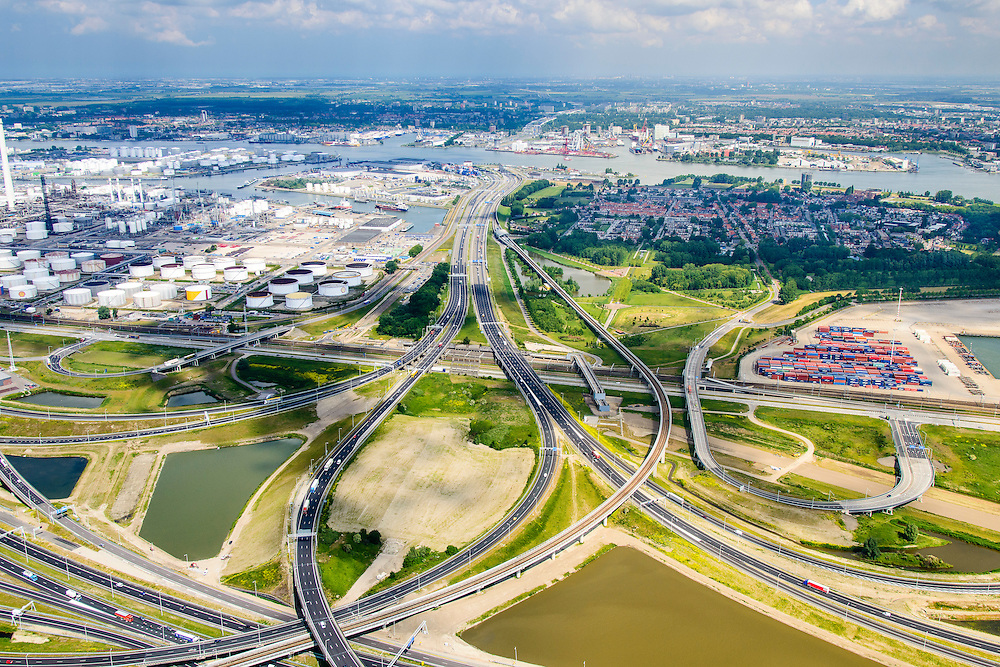 Nederland, Zuid-Holland, Rotterdam, 10-06-2015. A15 ter hoogte van knooppunt Benelux. A15 met Benneluxtunnel onder de Nieuwe Maas aan de horizon, links Pernis met Shell raffinaderij. Betuweroute en leidingenviaduct.<br /> Motorway A15, connecting Port of Rotterdam with hinterland, harbours and container terminals.<br /> luchtfoto (toeslag op standard tarieven);<br /> aerial photo (additional fee required);<br /> copyright foto/photo Siebe Swart.