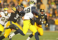 November 23 2013: Michigan Wolverines quarterback Devin Gardner (98) tries to hold off Iowa Hawkeyes defensive back John Lowdermilk (37) as he scrambles with the ball during the first quarter of the NCAA football game between the Michigan Wolverines and the Iowa Hawkeyes at Kinnick Stadium in Iowa City, Iowa on November 23, 2013. Iowa defeated Michigan 24-21.