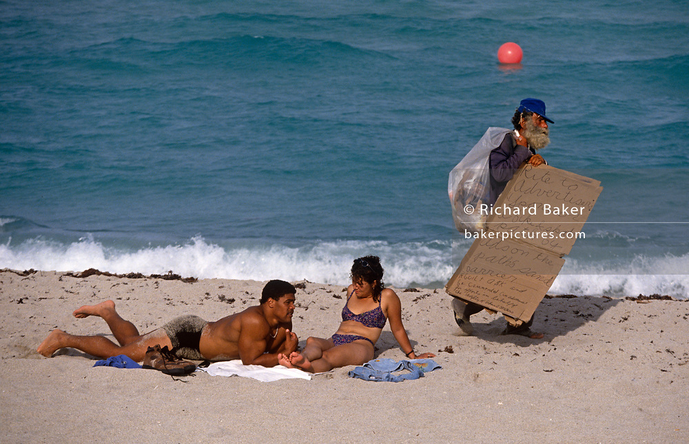 A wealthy Latino couple enjoy the beach as a man carrying possessions walks past, on 15th May 1996, in Miami Beach, Florida, USA.