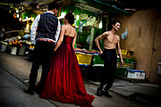 Hong Kong, China - Woman in a red velvet evening dress standing in a street with her boyfriend on May 01, 2018.