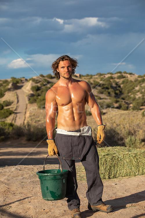 hot shirtless muscular tan man with a water bucket outdoors