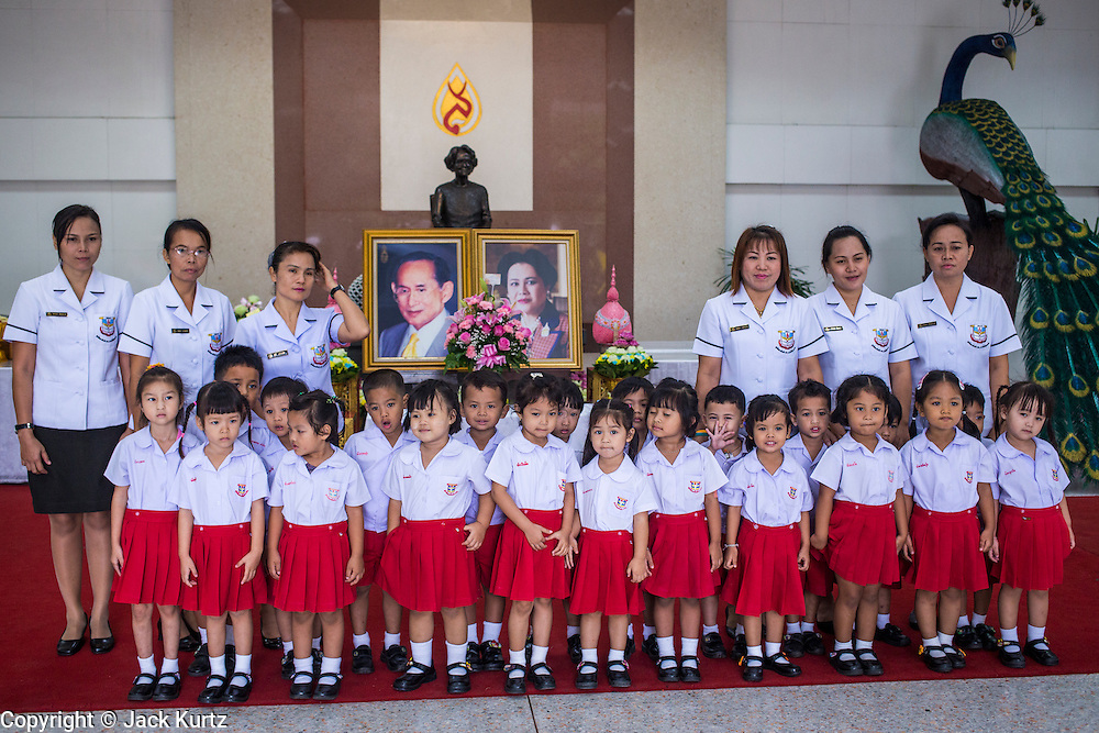 26 NOVEMBER 2012 - BANGKOK, THAILAND:   School children pose in front of picture of the King and Queen of Thailand after paying their respects to the monarchy at Siriraj Hospital in Bangkok. Siriraj was the first hospital in Thailand and was founded by King Chulalongkorn in 1888. It is named after the king's 18-month old son, Prince Siriraj Kakuttaphan, who had died from dysentery a year before the opening of the hospital. It's reported to one of the best hospitals in Thailand and has been home to Bhumibol Adulyadej, the King of Thailand, since 2009, when he was hospitalized to treat several ailments. Since his hospitalization tens of thousands of people have come to pay respects and offer get well wishes. The King's 85th birthday is on Dec 5 and crowds at the hospital are growing as his birthday approaches. The King is much revered throughout Thailand and is seen as unifying force in the politically fractured country.      PHOTO BY JACK KURTZ