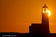 Setting sun behind Oregon's oldest lighthouse at Cape Blanco State Park, Oregon USA